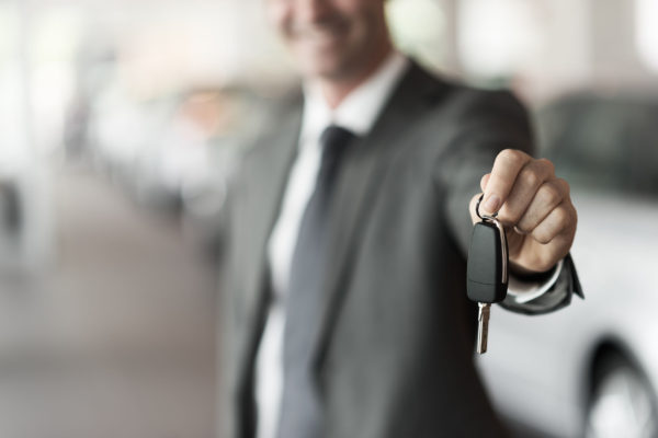 smiling car salesman handing over car keys